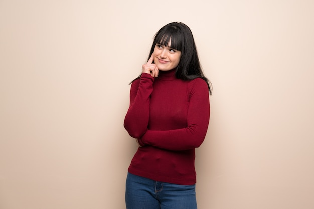 Young woman with red turtleneck thinking an idea while looking up