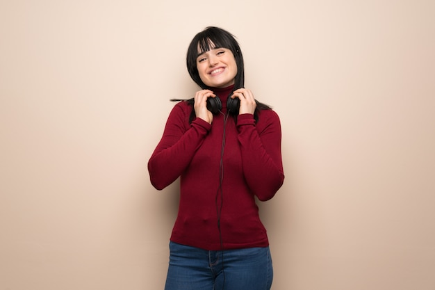 Young woman with red turtleneck with headphones