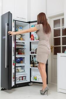 冷蔵庫を持つ若い女性