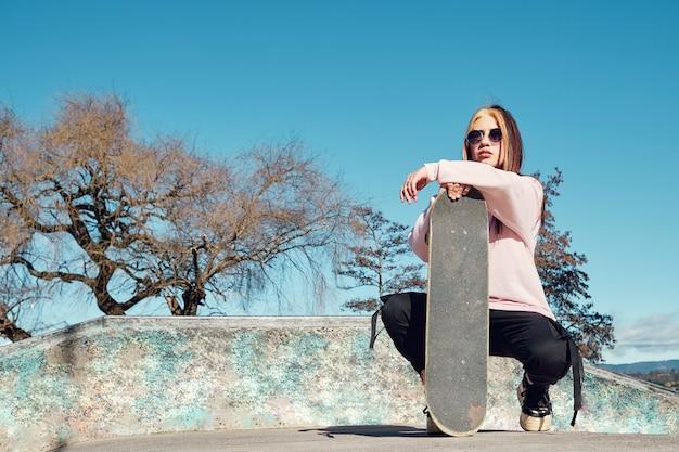 Молодая женщина в модных ретро очках сидит со своим скейтбордом, позирует в скейт-парке на фоне голубого неба