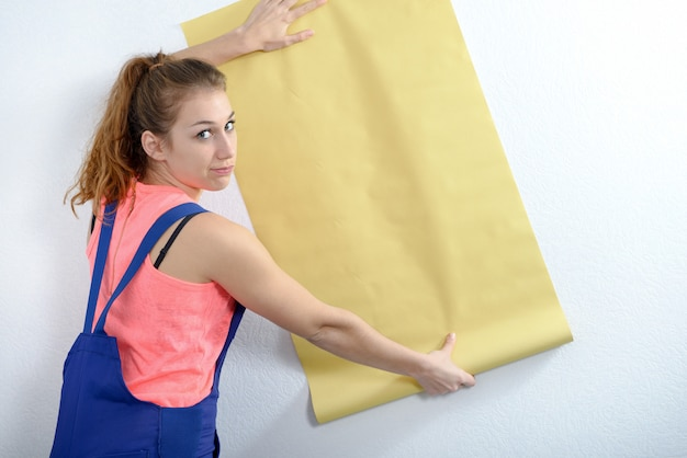 Young woman with a roll of yellow wallpaper