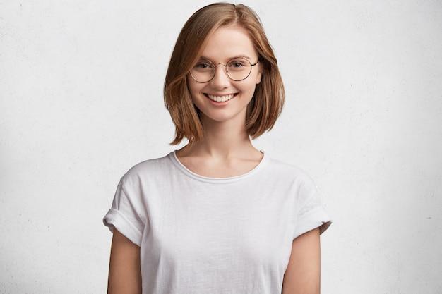 둥근 안경과 흰색 티셔츠와 젊은 여자