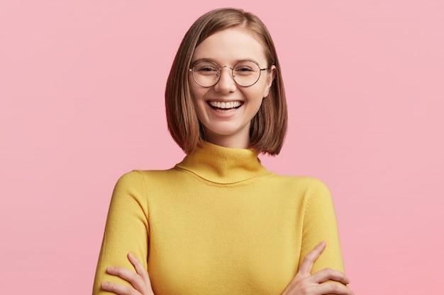 丸いメガネと黄色いセーターを持つ若い女性