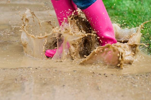 Молодая женщина с резиновыми сапогами прыгает в луже