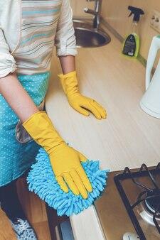 Молодая женщина с резиновыми перчатками, уборка кухни
