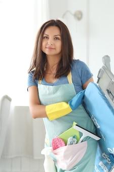 Giovane donna con guanti di gomma, pronta per la pulizia