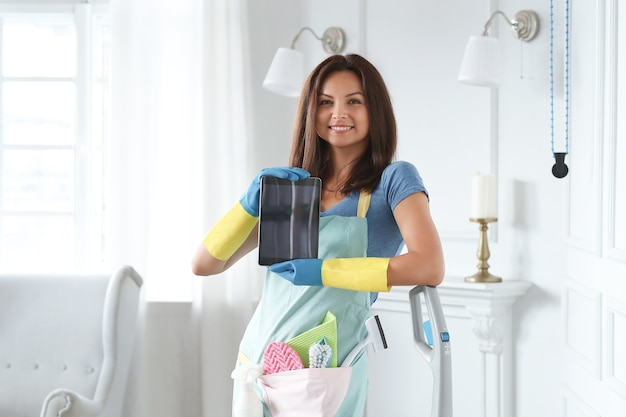 Young woman with rubber gloves showing tablet