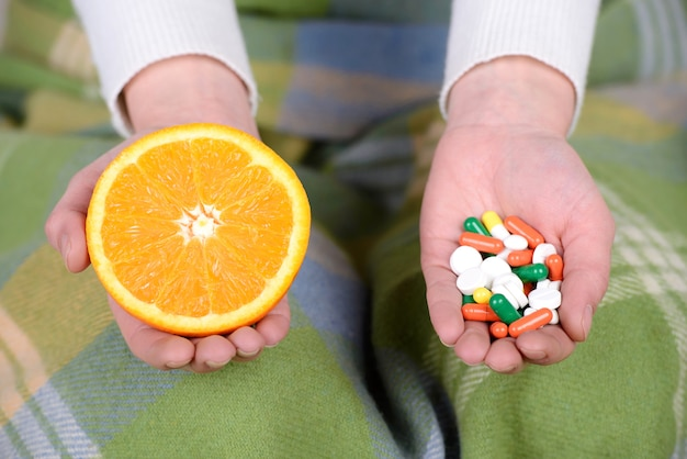 Young woman with a runny nose keep medicines and fruits.