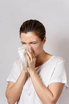 Young woman with a runny nose symptom is blowing into the paper tissue