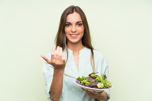 Young woman with salad inviting to come with hand. happy that you came