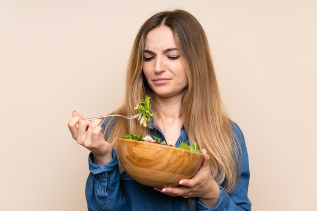 Young woman with salad over isolated background