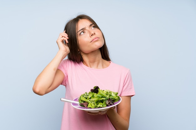 Young woman with salad over isolated blue wall having doubts and with confuse face expression