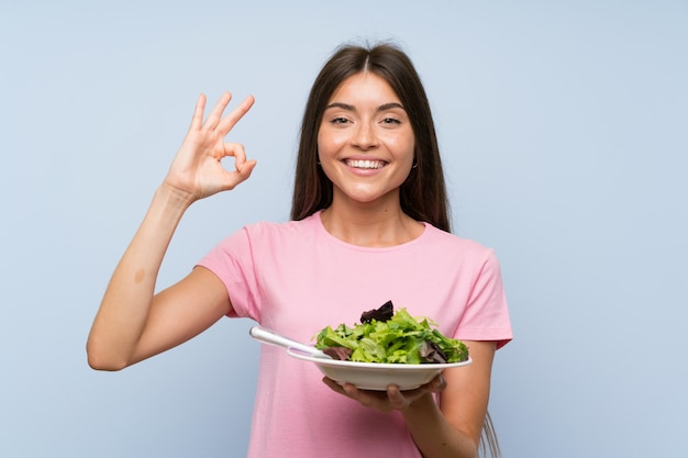 Young woman with salad over isolated blue wall showing ok sign with fingers