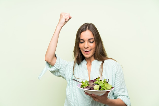 Young woman with salad over isolated green wall celebrating a victory