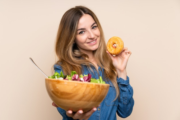 Young woman with salad over isolated wall and holding a donut