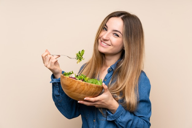 Young woman with salad over isolated wall