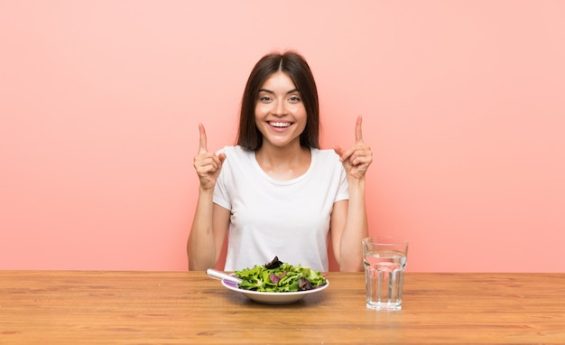 Young woman with a salad pointing up a great idea
