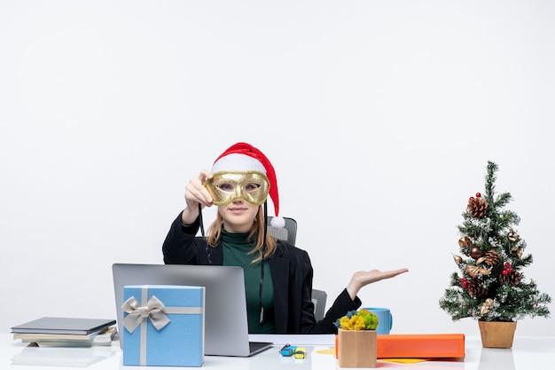 クリスマスツリーとギフトとテーブルに座っているサンタクロースの帽子とマスクを持つ若い女性