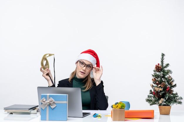 Giovane donna con occhiali cappello di babbo natale e tenendo la maschera seduto a un tavolo con un albero di natale e un regalo
