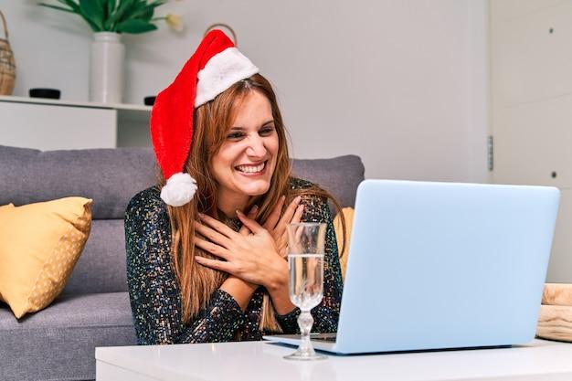 Молодая женщина в шляпе санта-клауса делает видеозвонок своей семье, чтобы отпраздновать рождество