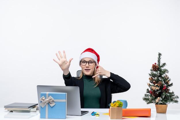 クリスマスツリーとギフトとテーブルに座っているサンタクロースの帽子を持つ若い女性