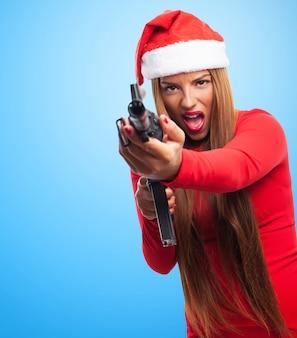 サンタの帽子とピストルを持つ若い女性