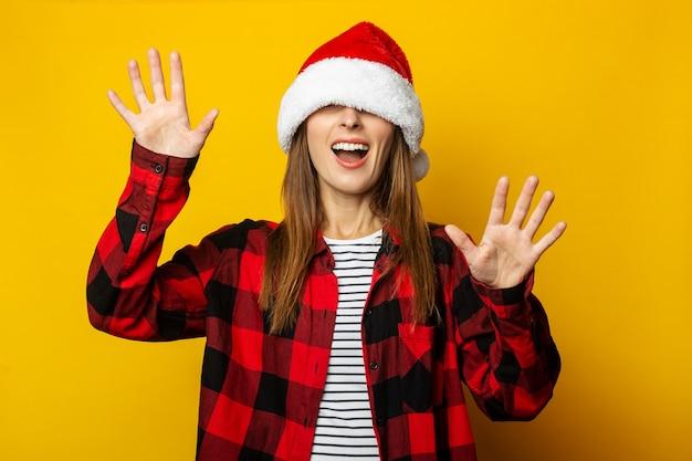 Молодая женщина в шляпе санта-клауса и красной клетчатой рубашке