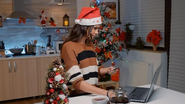 オンラインショッピングをしているサンタ帽子を持つ若い女性