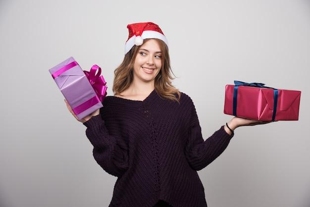 선물 상자를 들고 산타 모자와 젊은 여자를 선물한다.