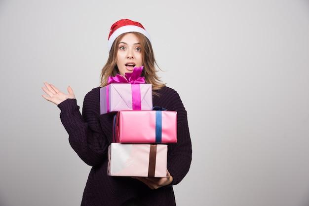 ギフトボックスを保持しているサンタの帽子を持つ若い女性がプレゼントします。 無料写真