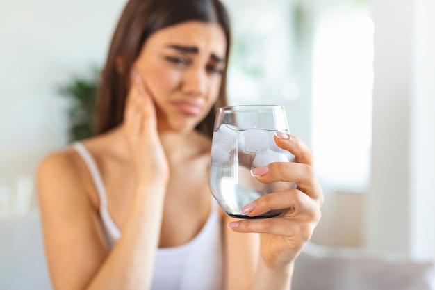 敏感な歯と氷と冷たい水のガラスを保持している手を持つ若い女性。ヘルスケアの概念。冷たい飲み物を飲む女性、角氷でいっぱいのガラスと歯痛、痛みを感じる