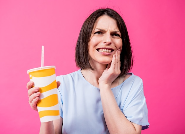 Young woman with sensitive teeth drinking cold water on color background