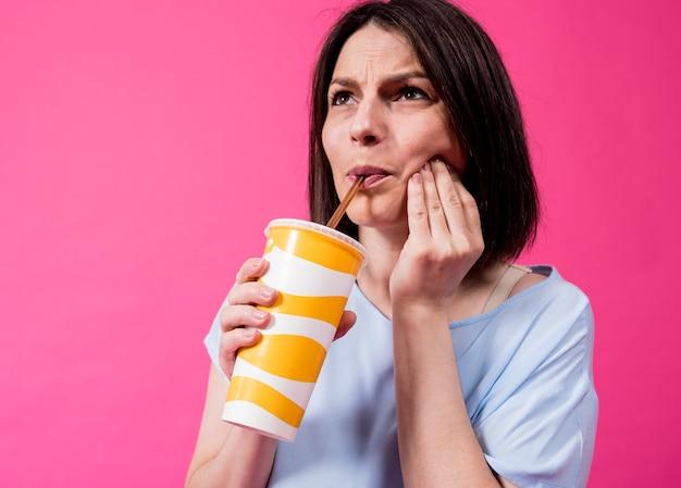 色の背景に冷たい水を飲む敏感な歯を持つ若い女性