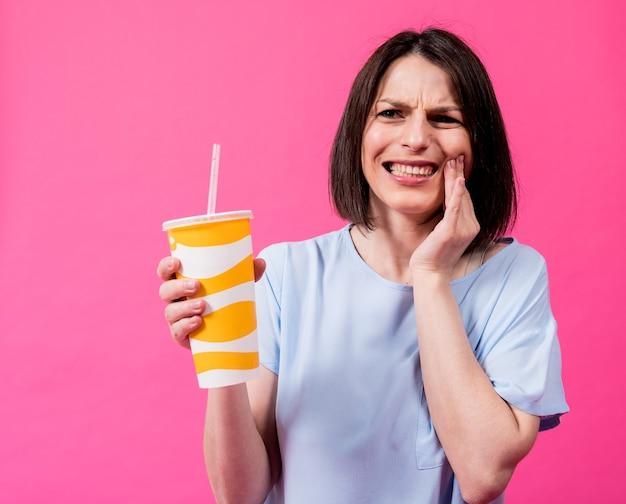 Молодая женщина с чувствительными зубами пьет холодную воду на цветном фоне