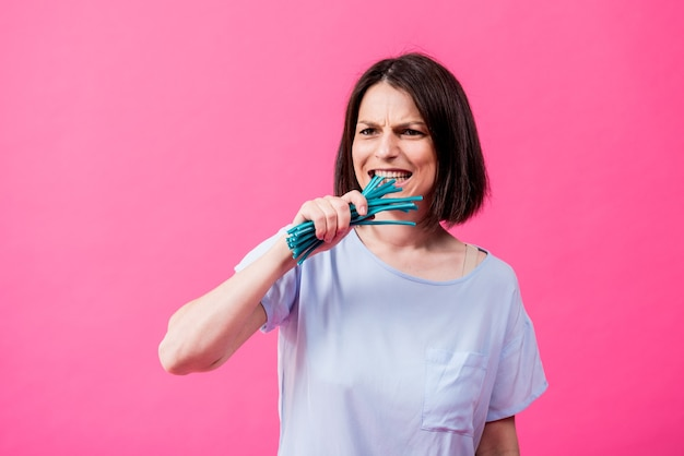 Young woman with sensitive teeth eating sweet candies on color background