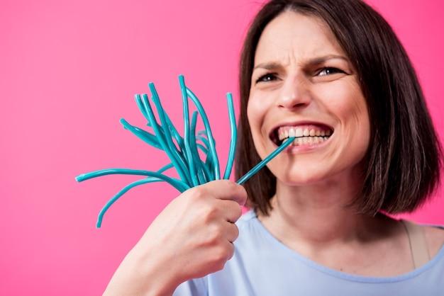 色の背景に甘いキャンディーを食べる敏感な歯を持つ若い女性