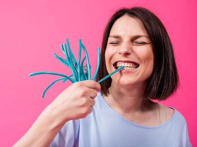 Молодая женщина с чувствительными зубами ест сладкие конфеты на цветном фоне