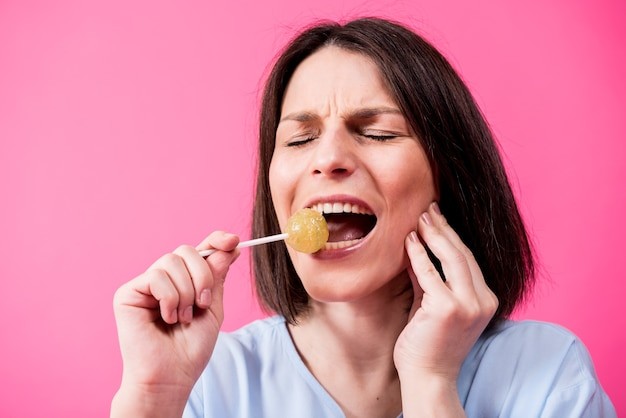 Young woman with sensitive teeth eating sweet lollipop on color background
