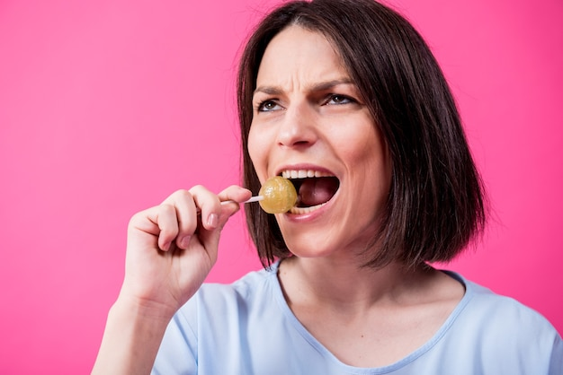 色の背景に甘いロリポップを食べる敏感な歯を持つ若い女性 Premium写真