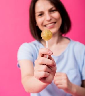 色の背景に甘いロリポップを食べる敏感な歯を持つ若い女性