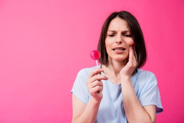 Молодая женщина с чувствительными зубами ест сладкий леденец на цветном фоне
