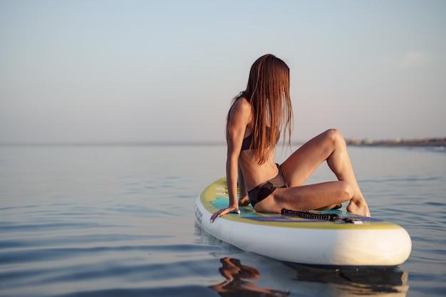 바다에서 패들 보드에 포즈 섹시 맞는 몸을 가진 젊은 여자, 클로즈업