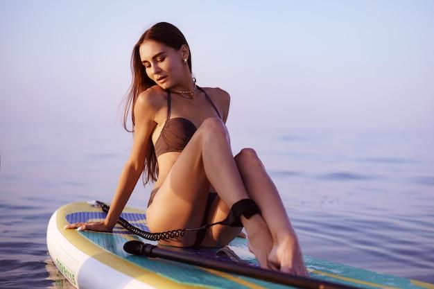 海のパドルボードでポーズをとってセクシーなフィットボディを持つ若い女性、クローズアップ
