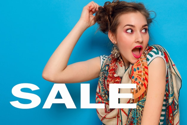 Young woman with shocked facial expression with sale sign