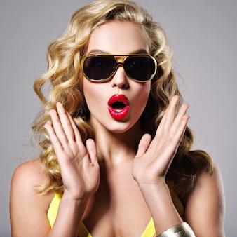Giovane donna con scioccato. ritratto di una ragazza caucasica sorpresa. attraente donna bionda espressiva - posa in studio