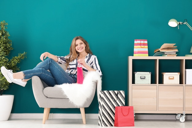 집에서 안락의자에 쇼핑백을 든 젊은 여성
