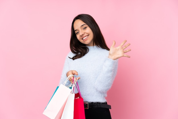 Young woman with shopping bag over isolated pink wall counting five with fingers