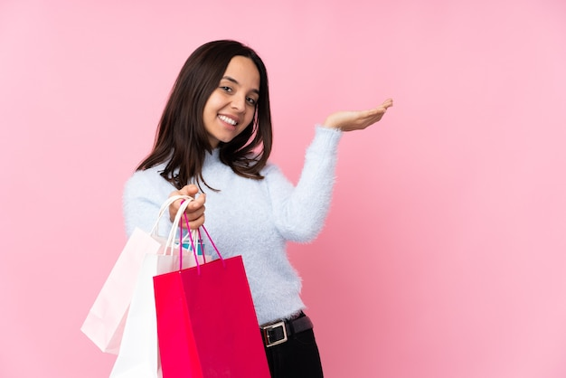 Young woman with shopping bag over isolated pink wall extending hands to the side for inviting to come