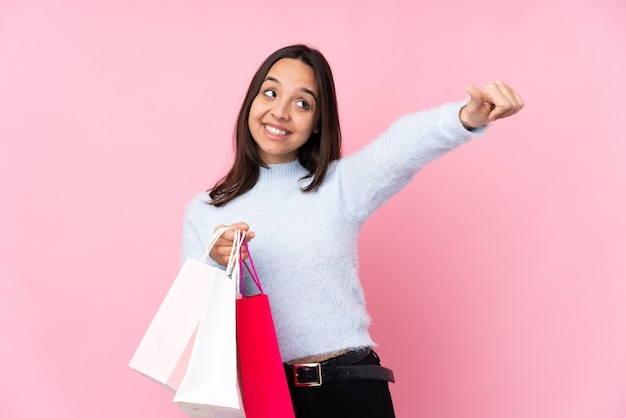 Young woman with shopping bag over isolated pink wall giving a thumbs up gesture