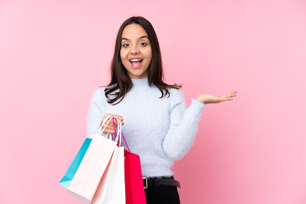 Young woman with shopping bag over isolated pink wall holding copyspace imaginary on the palm to insert an ad